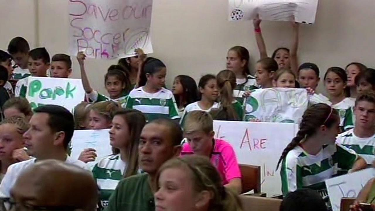 Kids hold up signs in support of the Santa Clara soccer fields next to Levis Stadium