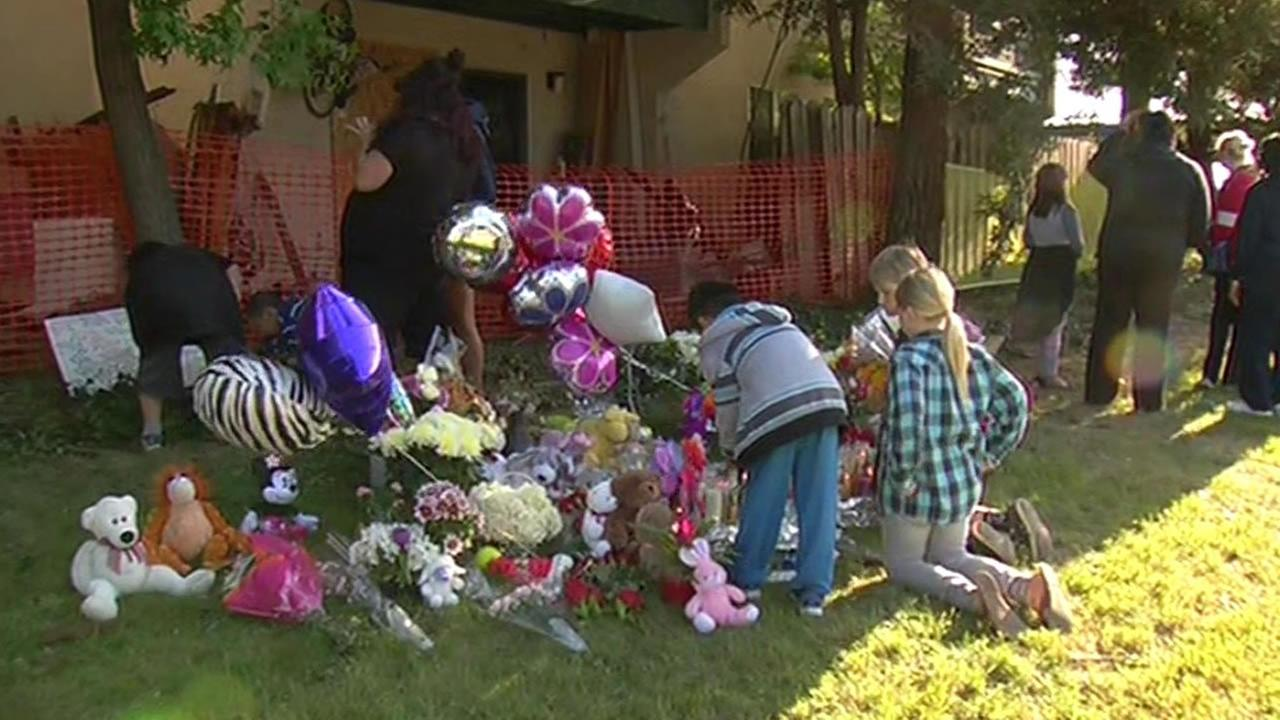 children gather near memorial with flowers and candles