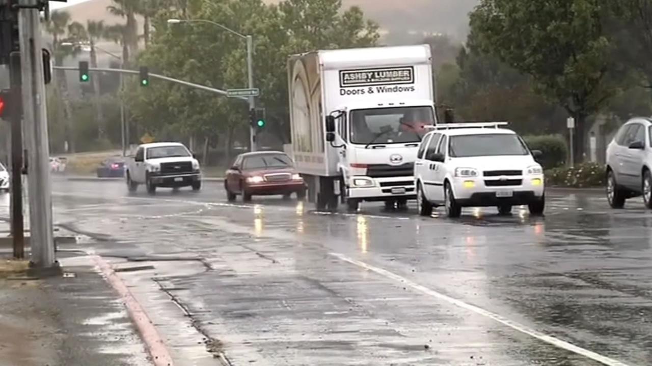 cars drive through the rain