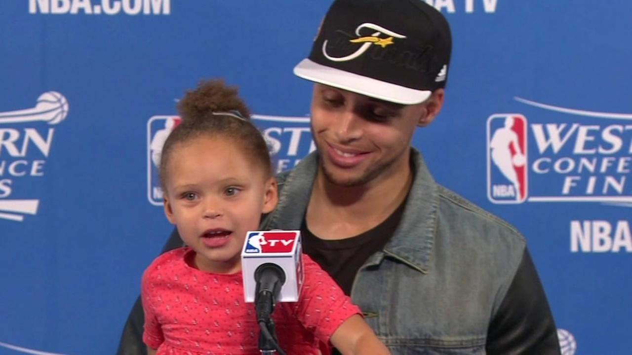 File photo - Warriors Stephen Curry speaks at a press conference while he hold his daughter.