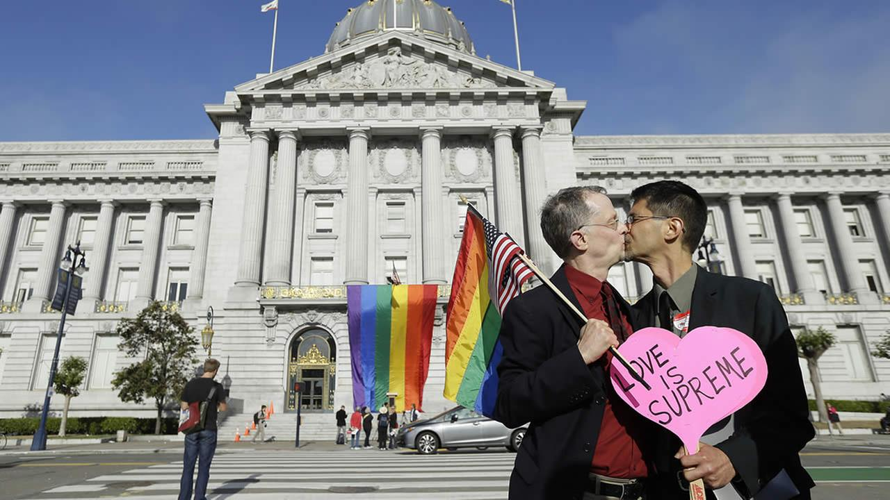 Gay rights advocates John Lewis, left, and his spouse Stuart Gaffney kiss across the street from City Hall in San Francisco, Friday, June 26, 2015. (AP Photo)