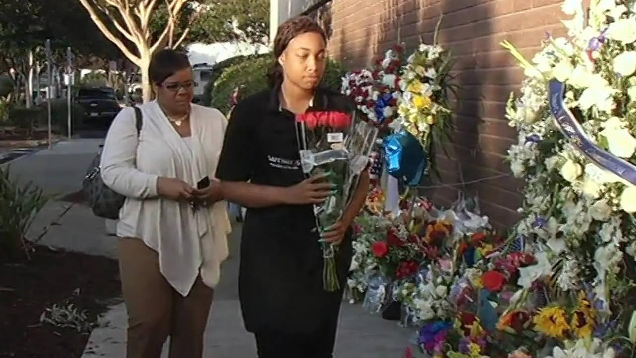 Alana Haskins brings flowers to the police station for fallen Hayward Sgt. Scott Lunger