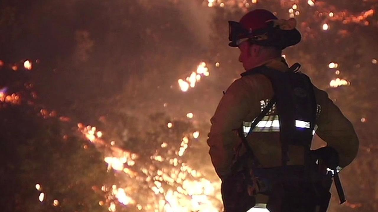 firefighter stands in front of Rocky Fire at night