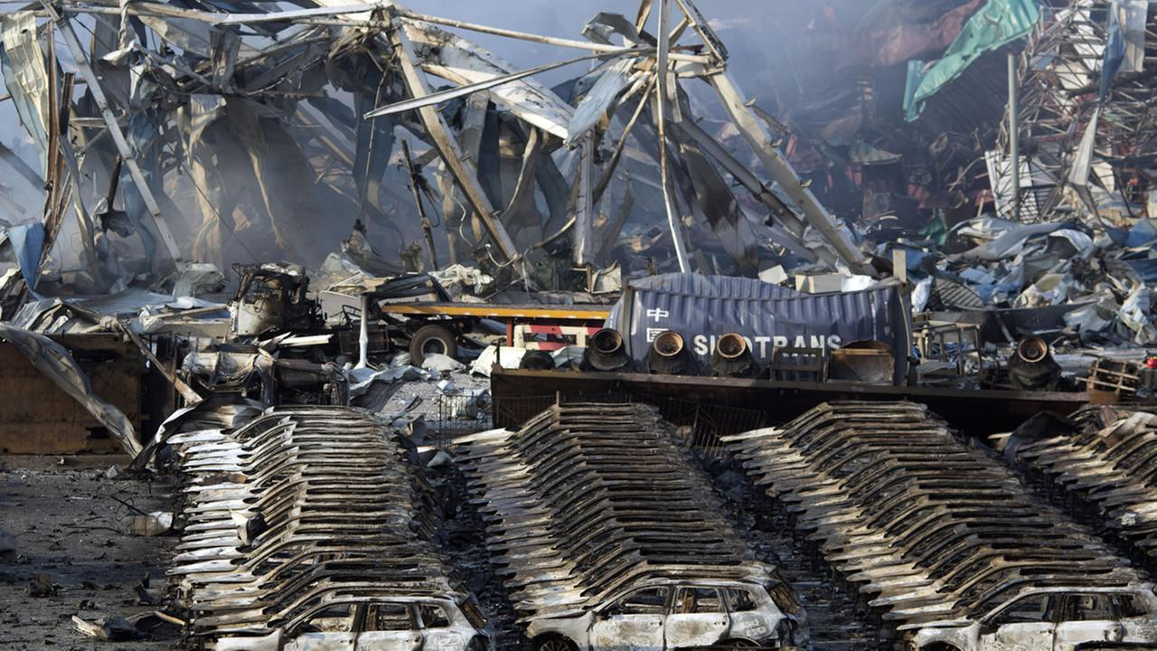 Charred remains of a warehouse and new cars are left burned after an explosion at a warehouse in northeastern Chinas Tianjin municipality, Thursday, Aug. 13, 2015.