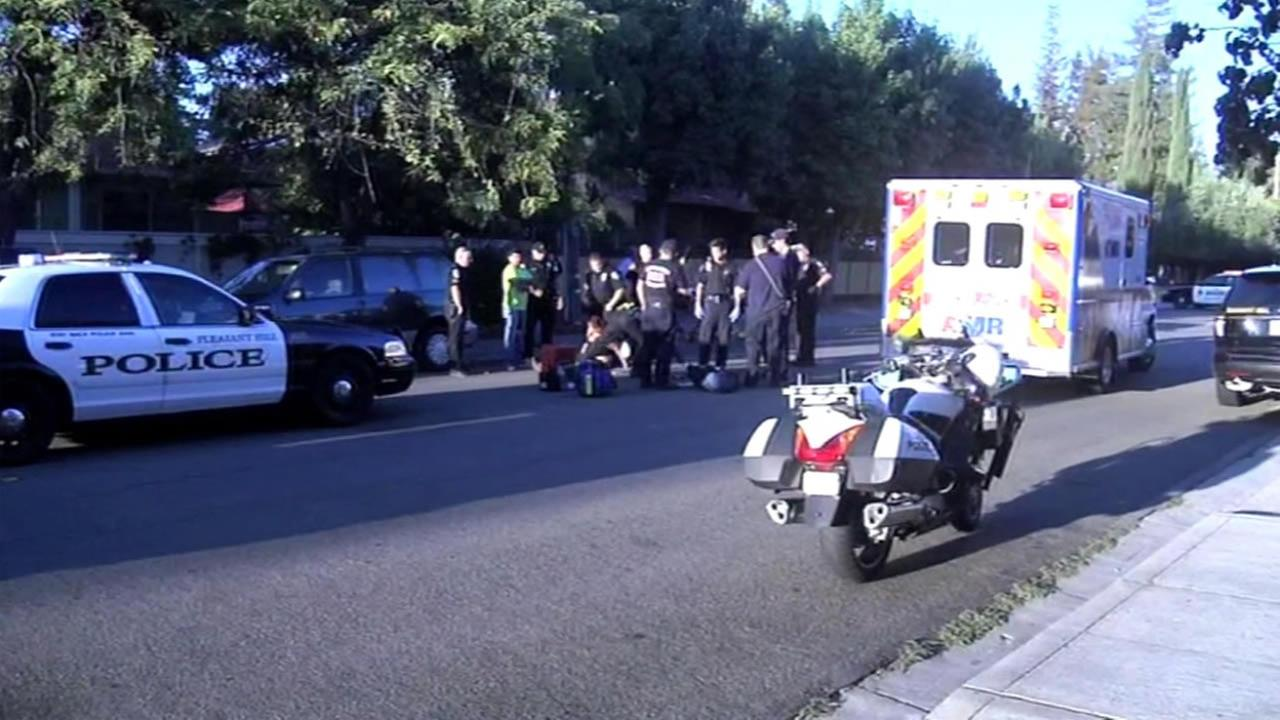 Paramedics treat a mother, who was injured, along with her three children, after being struck by a car in Pacheco, Calif., on Thursday, September 3, 2015.