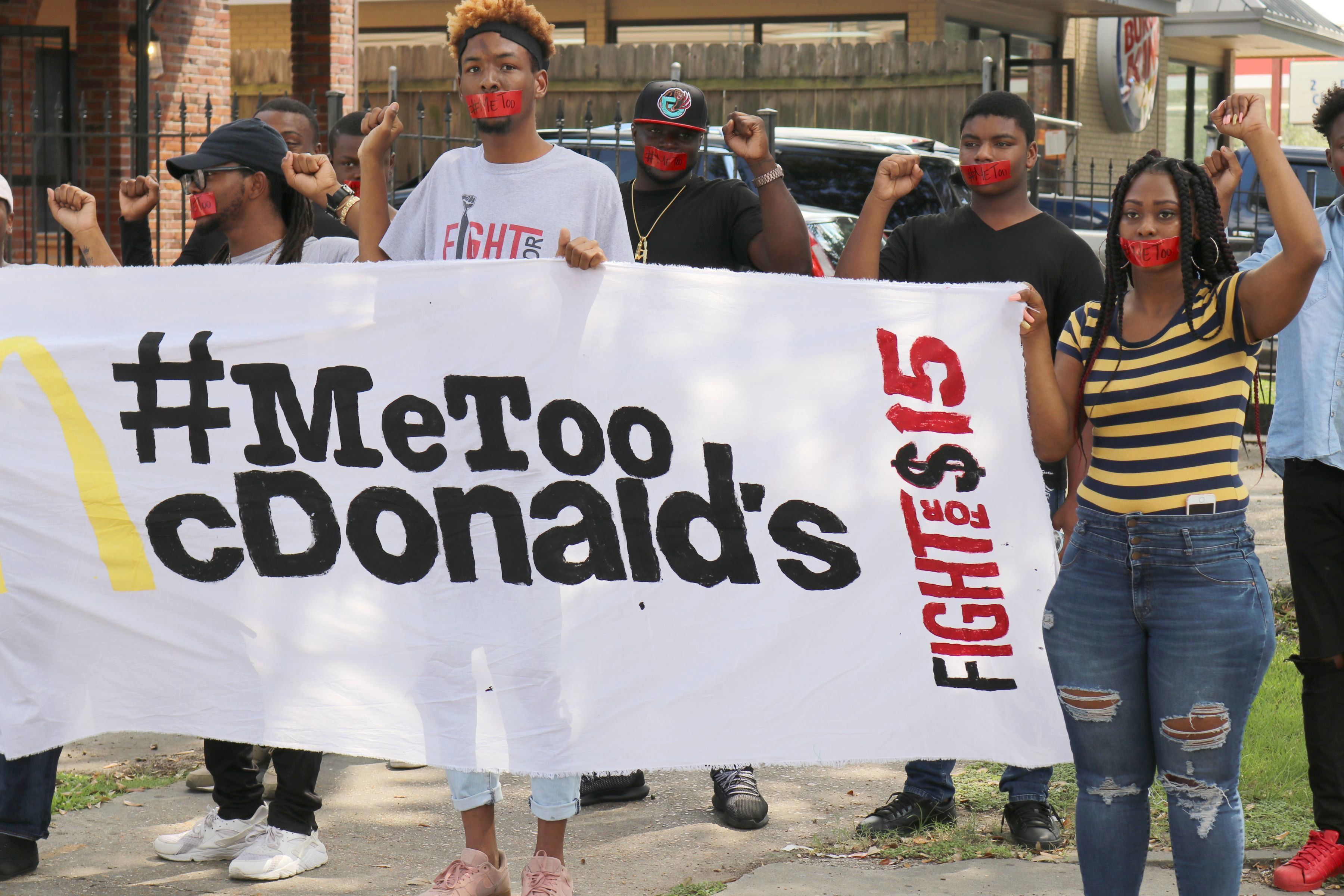 Current and former McDonalds employees wear tape with #MeToo over their mouths as they up to one of their restaurants for a protest in New Orleans on Tuesday, Sept. 18, 2018.