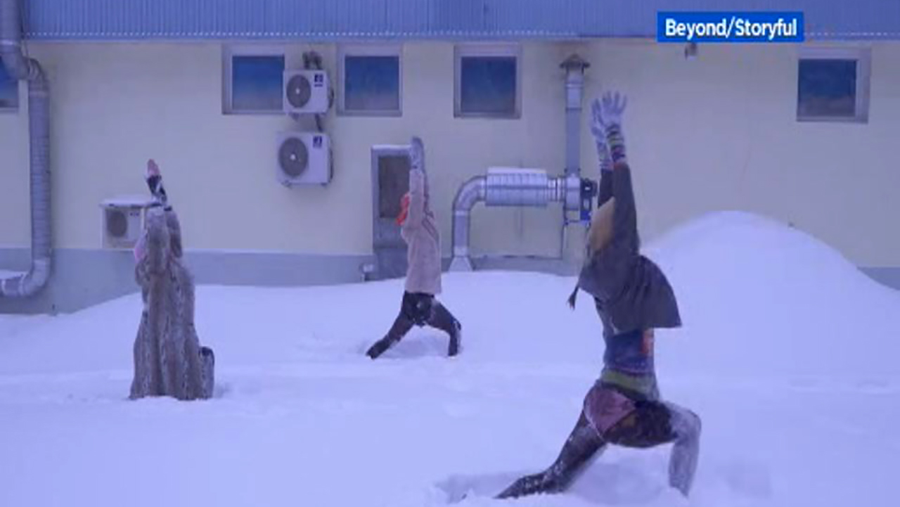 This image shows three woman practicing snowga or snow yoga in Moscow in January 2019.
