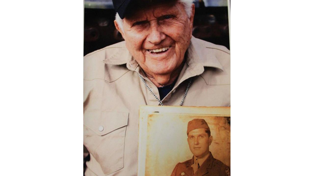 Troy D. Nolen holds a photo of his younger self during service in World War II. Nolen was assigned to the 1st Marine Division.