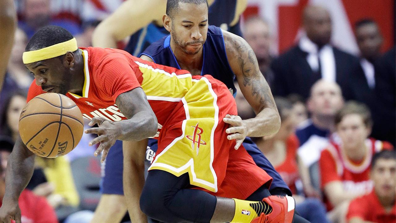 Houston Rockets Ty Lawson, left, is fouled by Dallas Mavericks Devin Harris in the first half of an NBA basketball game Saturday, Nov. 14, 2015, in Houston.