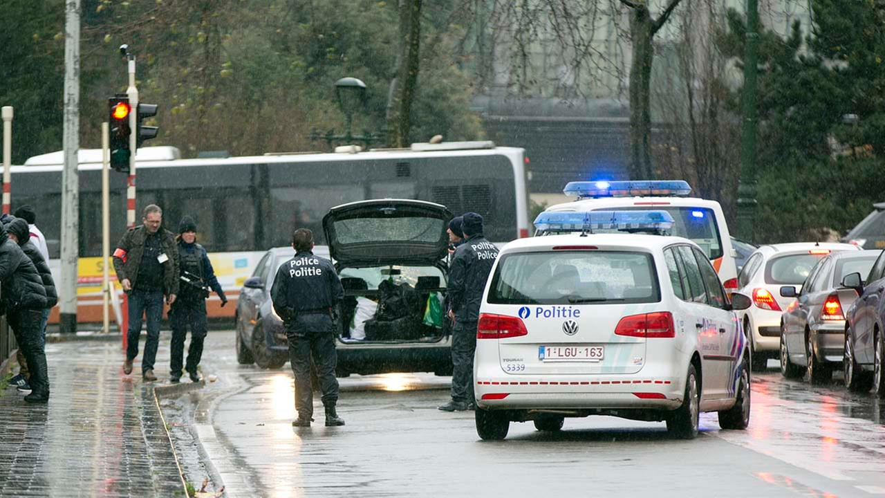 Police search the trunk of a car in Brussels, Saturday, Nov. 21, 2015.