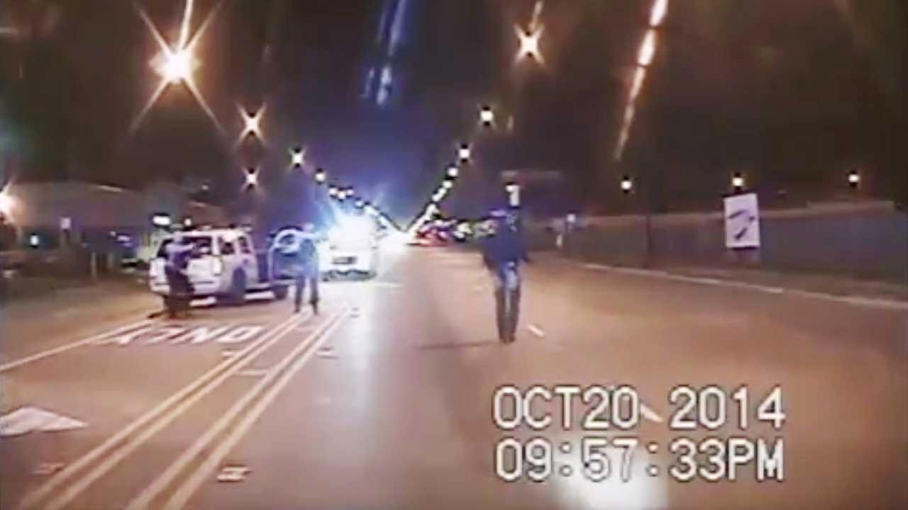 In this Oct. 20, 2014 frame from dash-cam video provided by the Chicago Police Department, Laquan McDonald, right, walks down the street moments before being shot by officer.