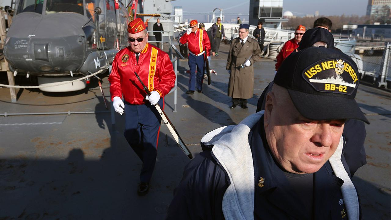 Volunteer worker on the battleship USS New Jersey arrive with others during a commemoration of the 74th anniversary of the attack on Pearl Harbor.