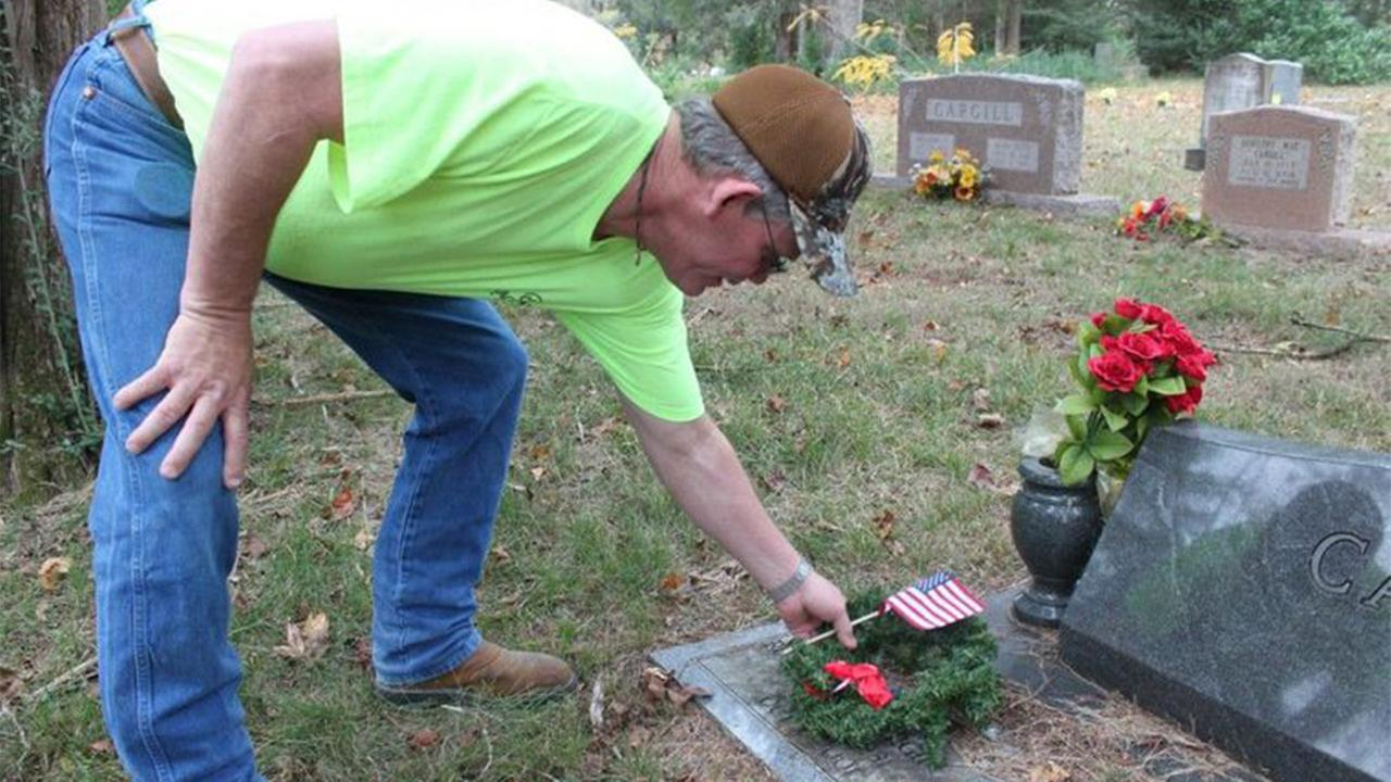 Dennis Thompson drove from Louisiana to join his family and the American Legion Auxiliary Post No. 618 in honoring veterans with 300 handmade christmas wreaths at Willis Cemetery.