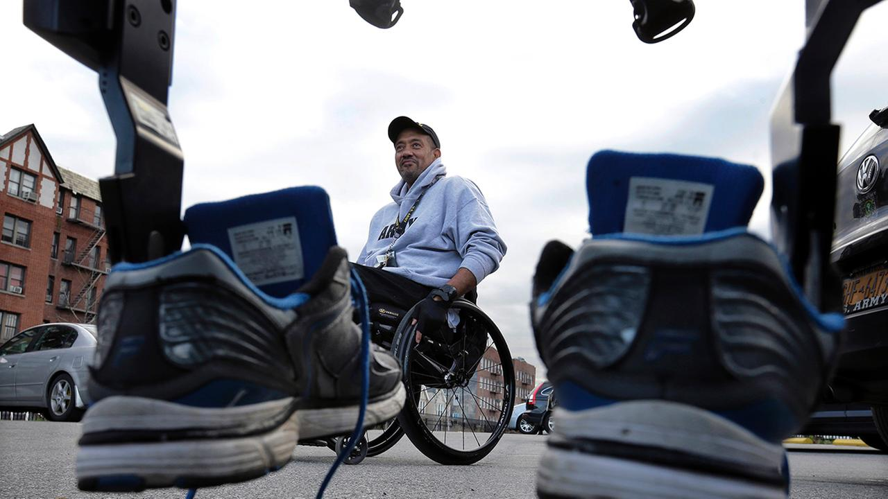 Paralyzed Army veteran Gene Laureanos sneakers are mounted on a ReWalk device as he prepares to use the machine to walk Wednesday, Dec. 16, 2015, in Bronx, N.Y.