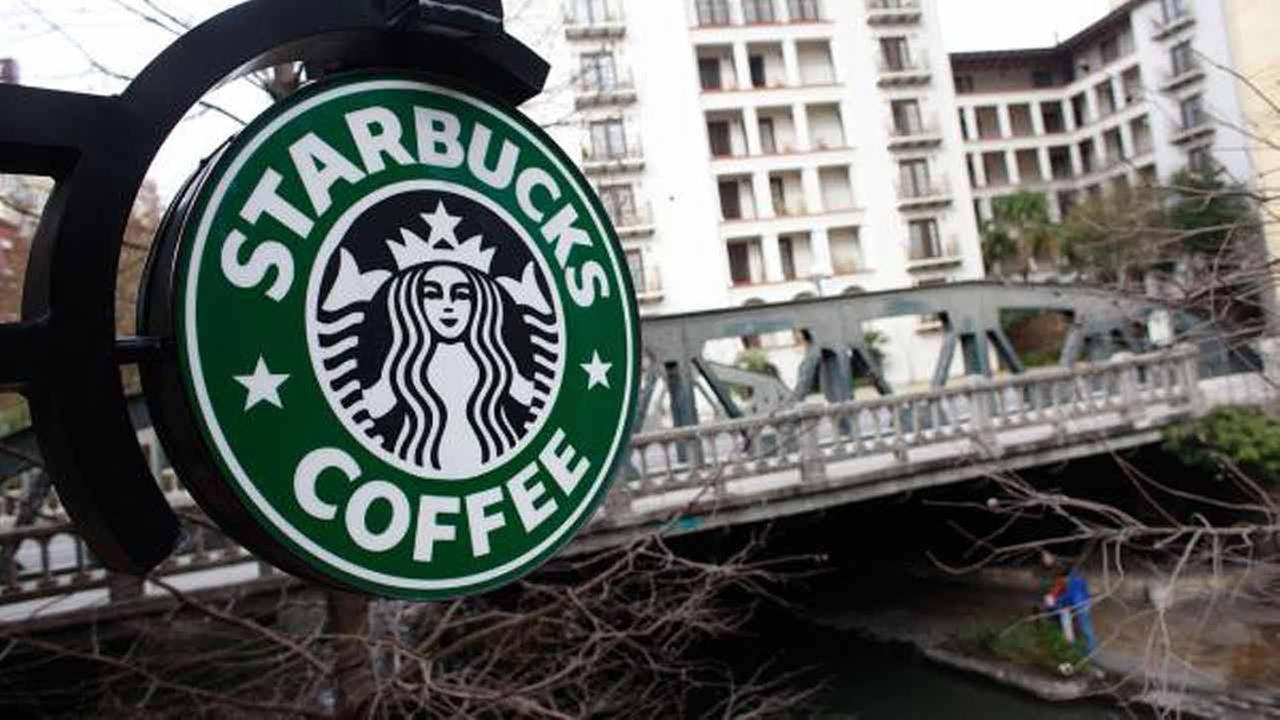 In this Feb. 14, 2010 photo, a sign outside a Starbucks hangs over the Riverwalk with the Navarro Street bridge in the background in San Antonio, Texas.