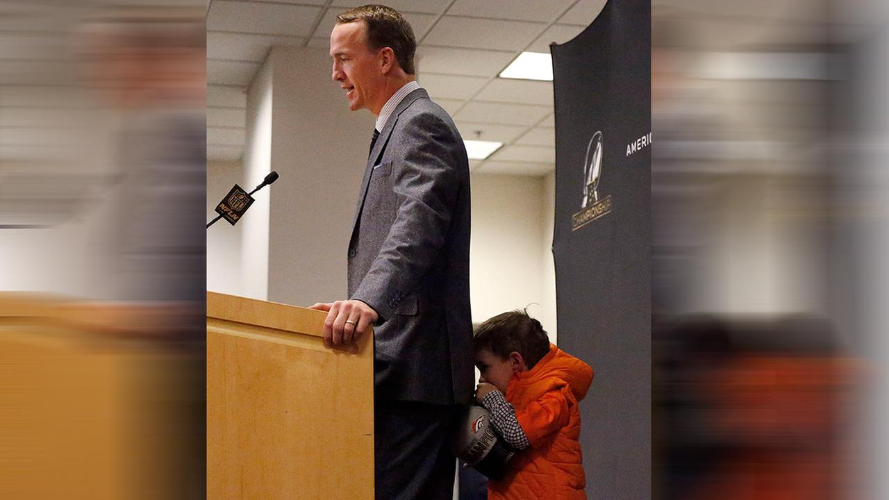 Denver Broncos quarterback Peyton Mannings son, Marshall, hides behind his father