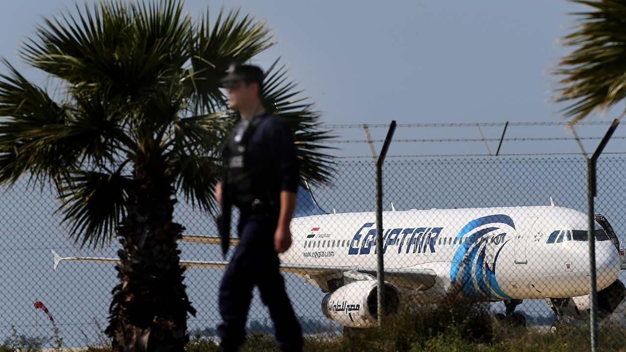 A police officer patrols outside the airport as an hijacked aircraft of EgyptAir is seen after landing at Larnaca Airport in Cyprus Tuesday, March 29, 2016.