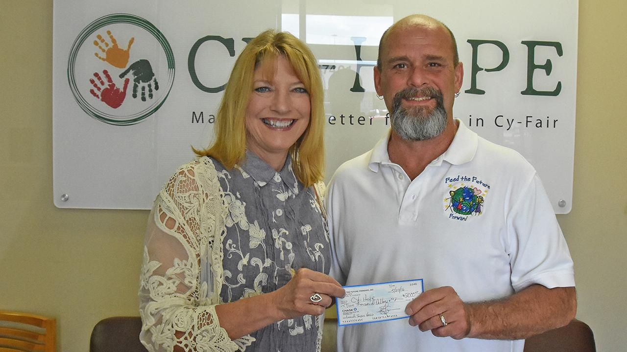 Lynda Zelenka, executive director of Cy-Hope, accepts a $2,000 check from Feed the Future Forwards Kenny Thompson to help fund the Lunch Super Hero program in CFISD.