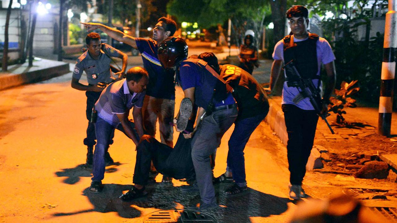 People help an unidentified injured person after a group of gunmen attacked a restaurant popular with foreigners in a diplomatic zone of Dhaka.