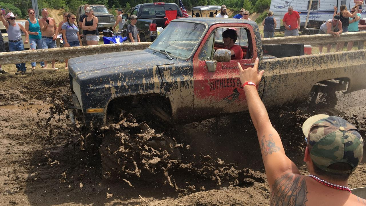 Spectators cheer as a pickup truck splashes through mud at an event formerly called the Redneck Olympics on Saturday, July 30, 2016, in Hebron, Maine.