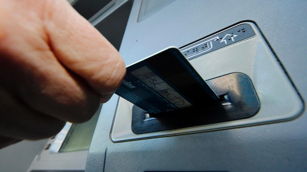 In this Saturday, Jan. 5, 2013 photo, a person demonstrates using a credit card in an ATM in Pittsburgh