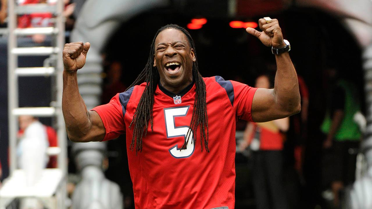 WWE wrestler and commentator Booker T reacts to the crowd before an NFL football game between the Baltimore Ravens and Houston Texans, Sunday, Oct. 21, 2012, in Houston.