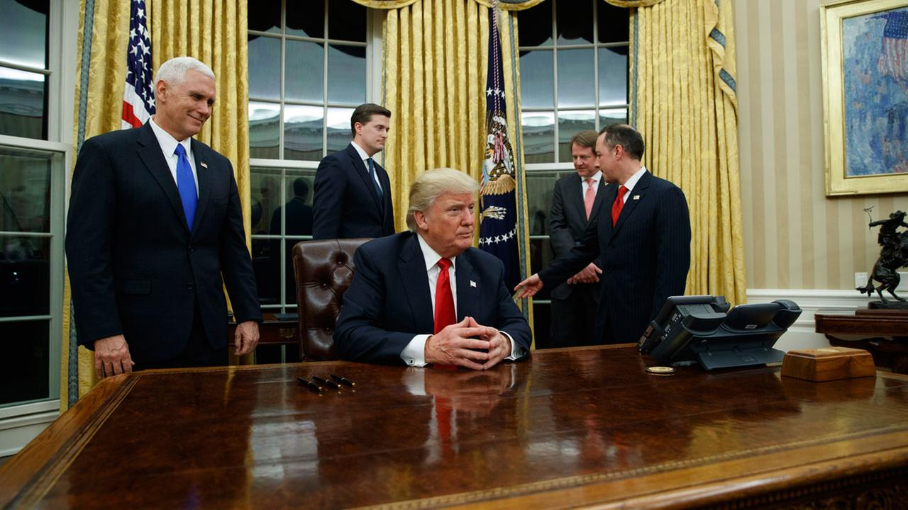 Vice President Mike Pence, left, watches as President Donald Trump prepares to sign his first executive order, Friday, Jan. 20, 2017, in the Oval Office of the White House.