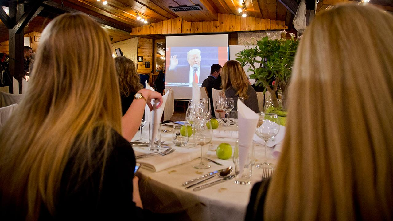 Guests watch a televised broadcast of inauguration of Donald Trump at a restaurant in Sevnica, Slovenia, Friday, Jan. 20, 2017. (AP Photo/Darko Bandic)