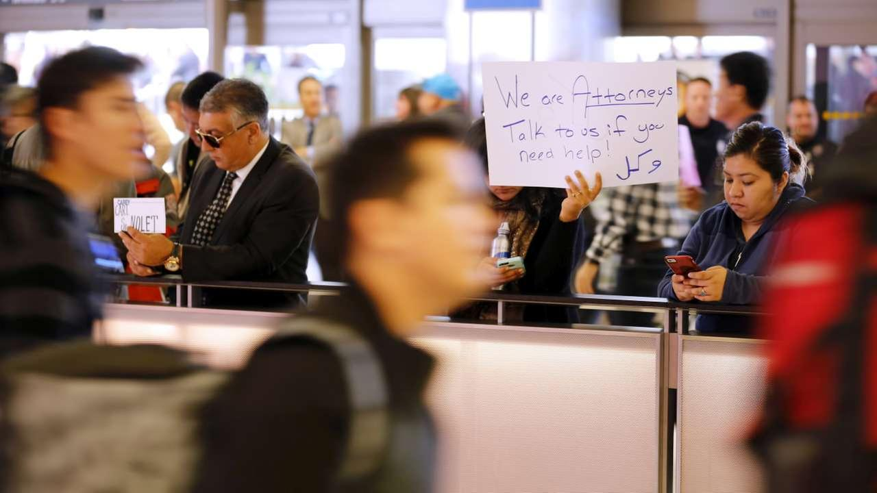 Attorney Sabra Gandhi holds up a sign while travelers pass by as protests against President Donald Trumps executive order banning travel from seven Muslim-majority countries