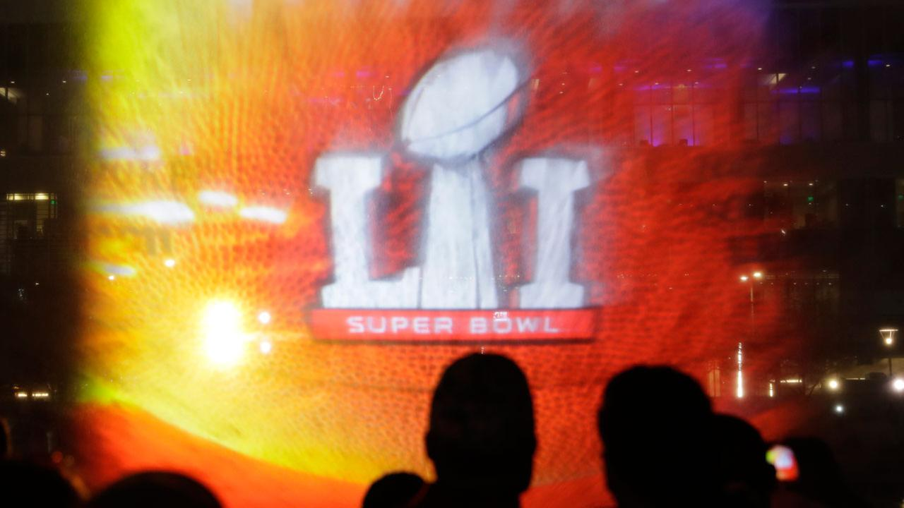Fans watch a 3D light show as it is projected on a water spray at Super Bowl Live for the NFL Super Bowl 51 football game Tuesday, Jan. 31, 2017, in downtown Houston.