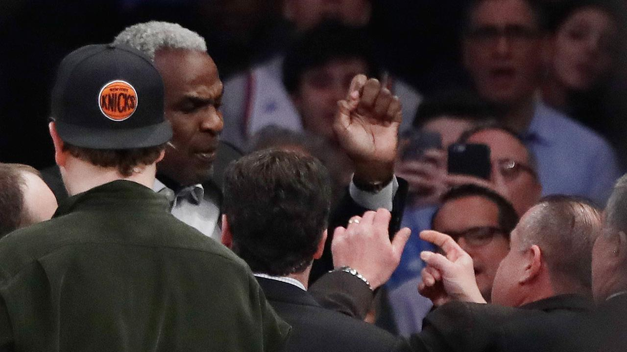 Former New York Knicks player Charles Oakley exchanges words with a security guard during the first half of an NBA basketball game between the New York Knicks and the LA Clippers W