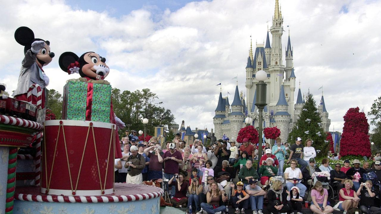 Visitors gather in front of Cinderellas Castle to watch Mickey and Minnie Mouse during the Christmas parade at Walt Disney Worlds Magic Kingdom in Lake Buena Vista, Fla.