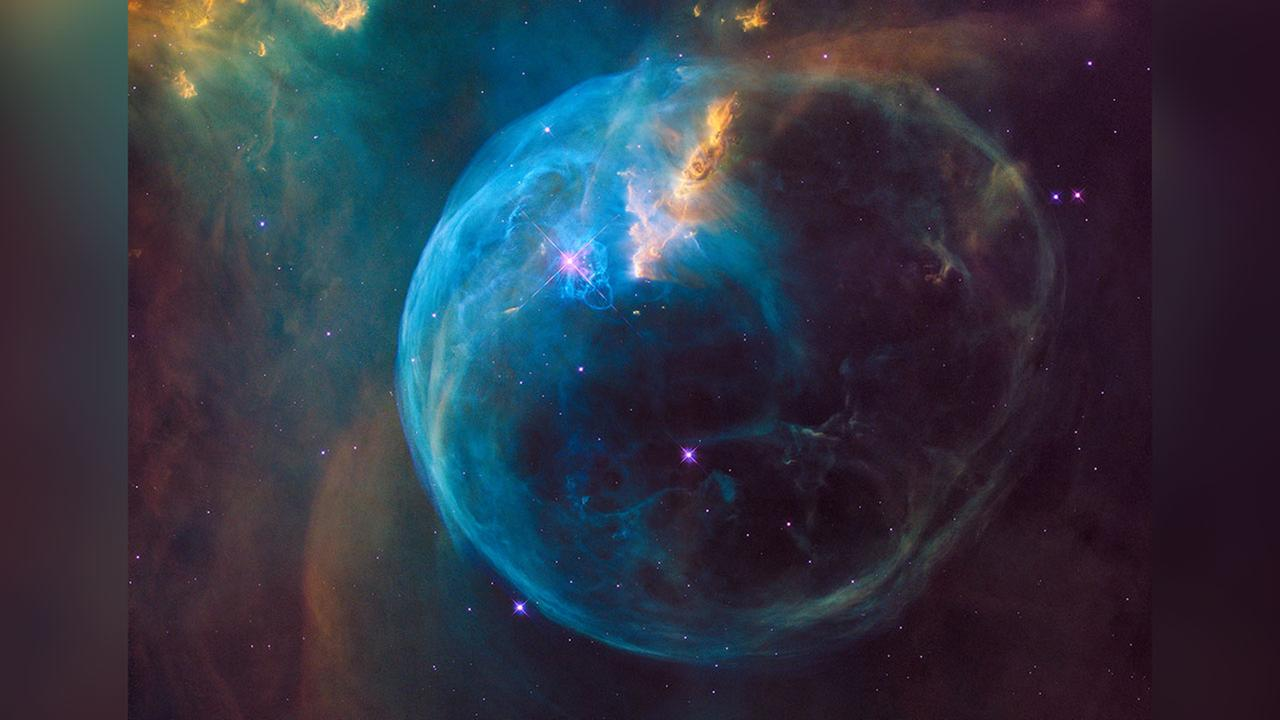 BUBBLE NEBULA: The remarkably spherical Bubble marks the boundary between an intense wind of particles from the star and the more quiescent  interior of the nebula.