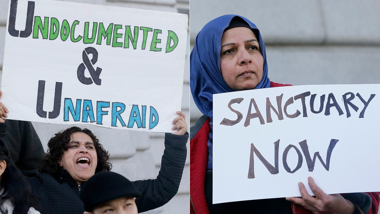 Lordes Reboyoso, left, and Moina Shaiq hold signs at a rally outside of City Hall in San Francisco, Wednesday, Jan. 25, 2017.