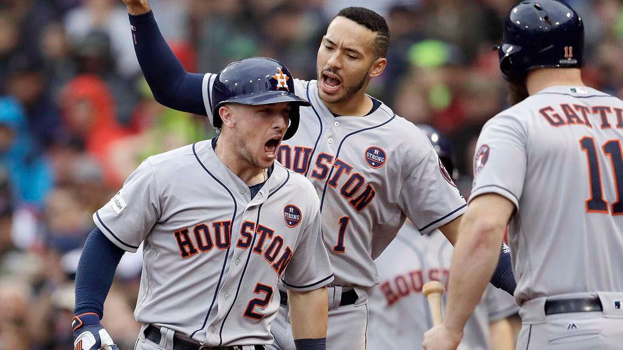 Houston Astros third baseman Alex Bregman (2) celebrates his home run with Carlos Correa, rear, and Evan Gattis, right during the eighth inning of Game 4.