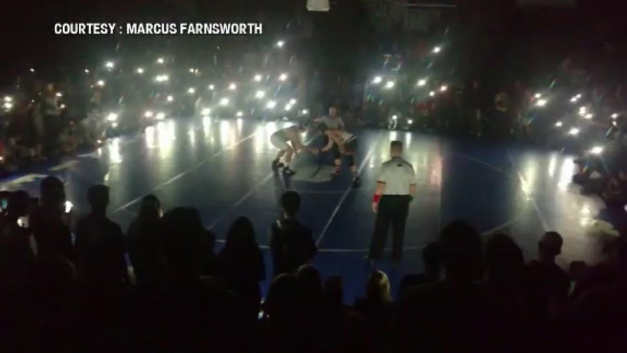 Parents and fans light high school wrestling match with their phones during power outage.