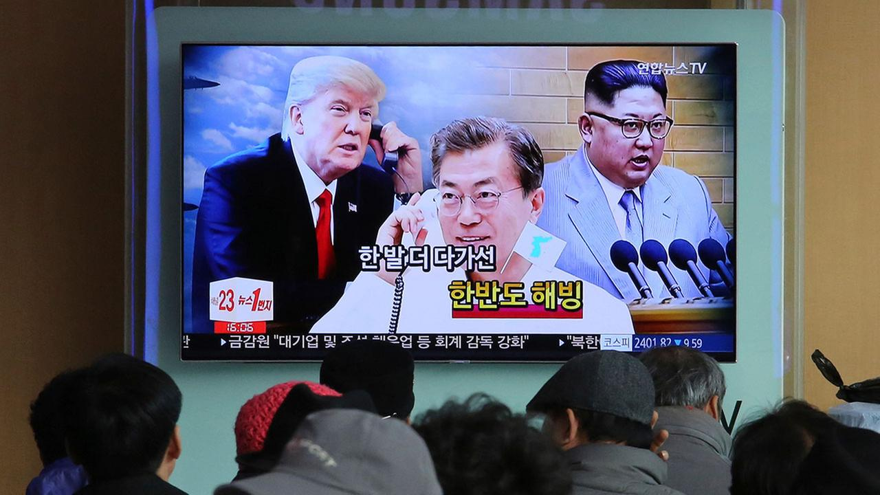 People watch a TV screen showing images of North Korean leader Kim Jong Un, right, South Korean President Moon Jae-in, center, and U.S. President Donald Trump.