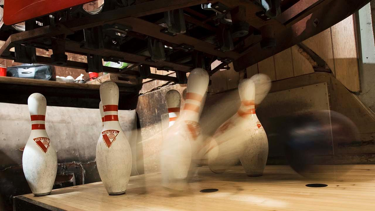 A ball hits some pins at a bowling alley