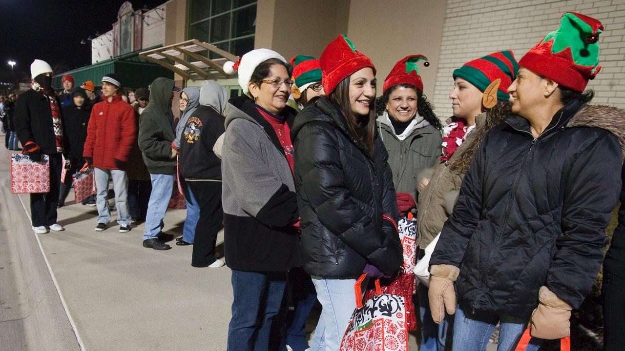 Shoppers with elf hats wait in line with others for the doors to open at a Target store on Black Friday, the traditional start of the holiday.