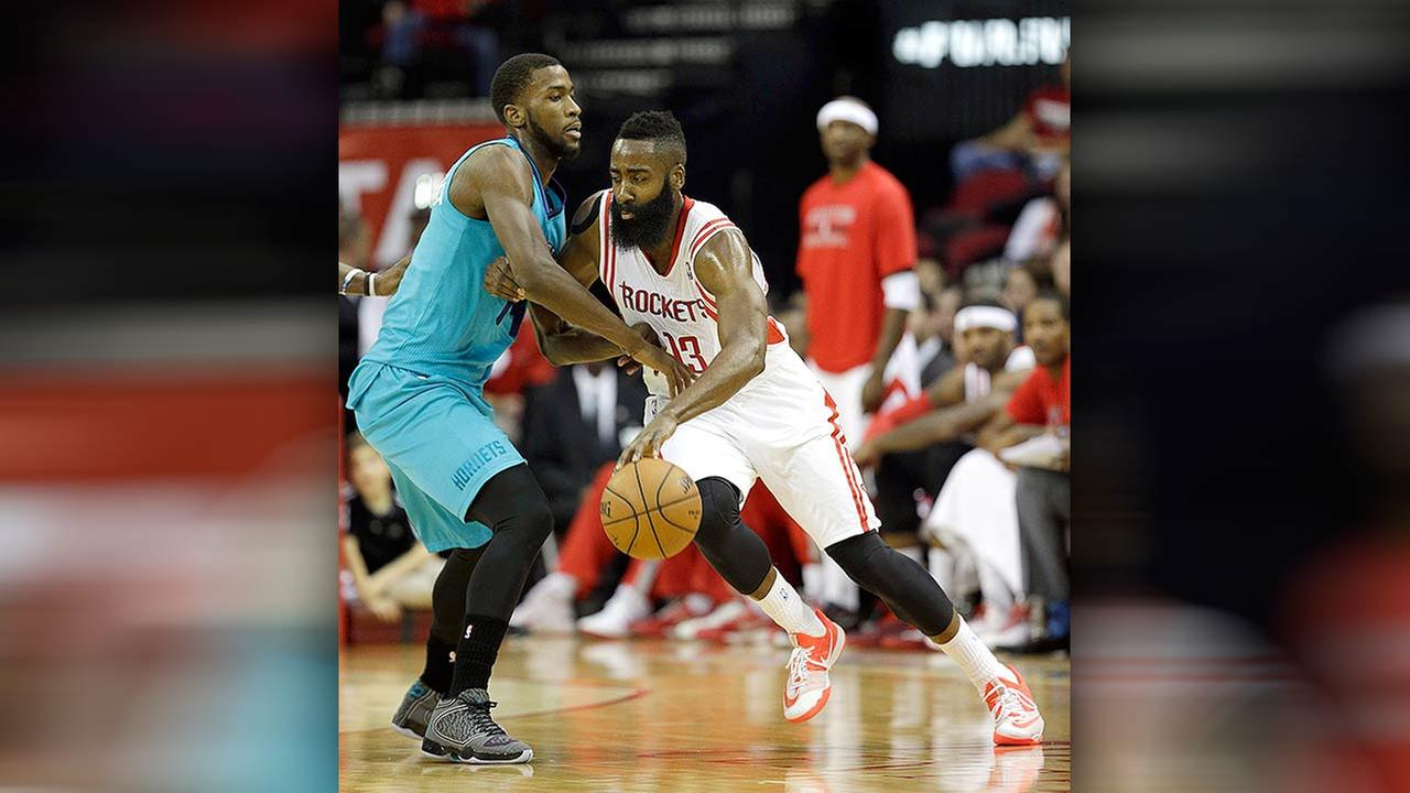 Houston Rockets James Harden (13) drives around Charlotte Hornets Michael Kidd-Gilchrist, left, during the first quarter of an NBA basketball game Wednesday, Dec. 31, 2014