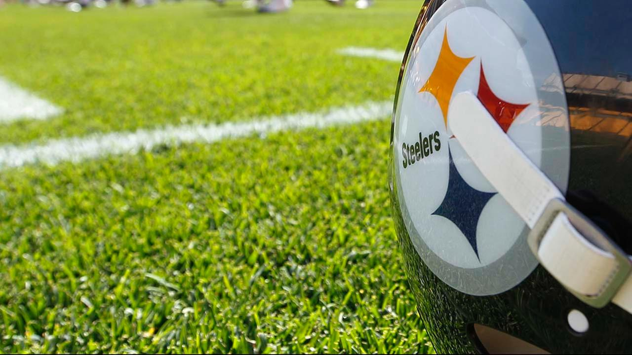A Pittsburgh Steelers football helmet sits by the sideline