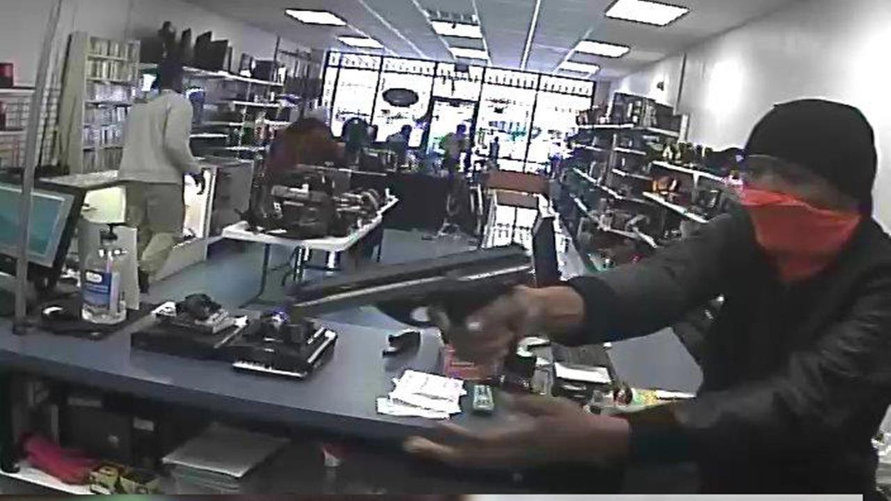 Pawn shop employee tries to arm herself in armed robbery; 4 sought in theft