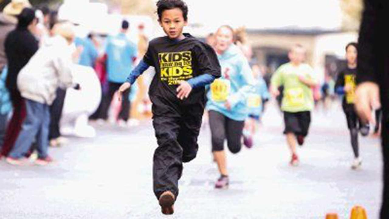 A runner crosses the finish line during the Kids Running for Kids fundraising event Saturday at Market Street in The Woodlands.