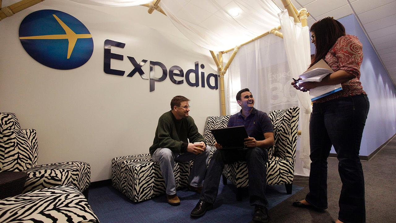 Expedia analytics team workers Mike Brown, left, Saurin Pandya and Prashanti Tata chat in an alcove set up for employees in Bellevue, WA.