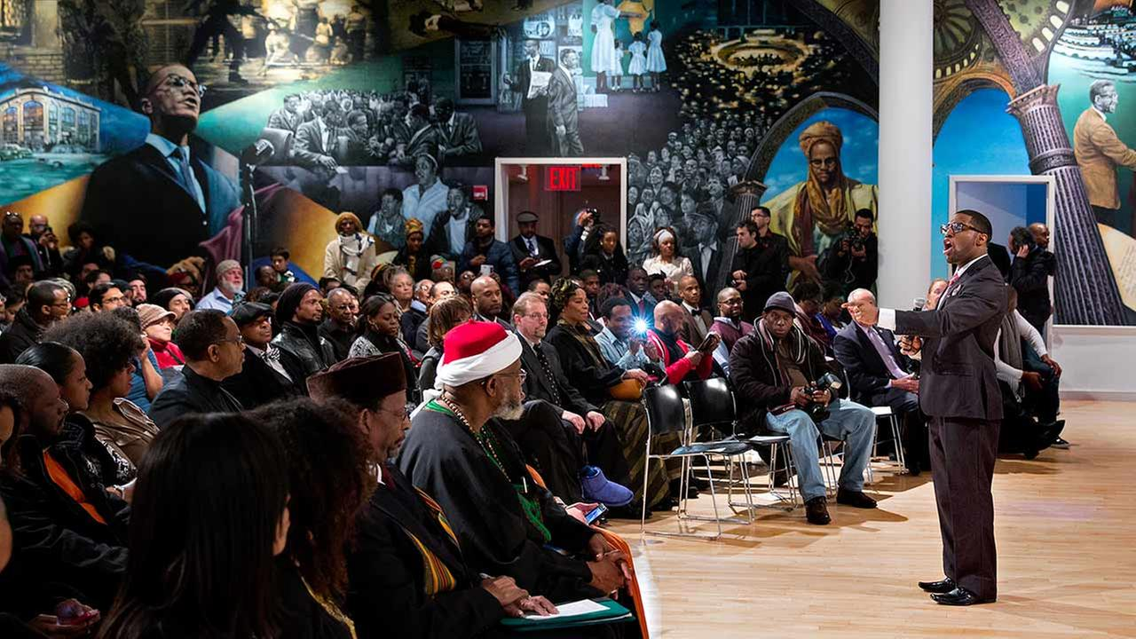 A mural depicting the lives of Malcolm X and his family is the backdrop for artist Jamel Hudson as he sings Saturday, Feb. 21, 2015.