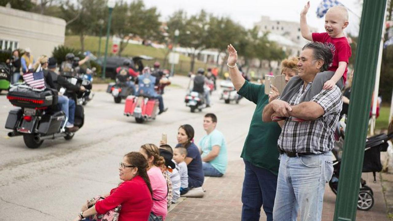 Conroe Go Texan Parade attendees wave and shoot videos as the Cut N Shoot Texas Chapter of the Harley Owners Group passes by during the 50th Annual Go Texan Parade Saturday in down