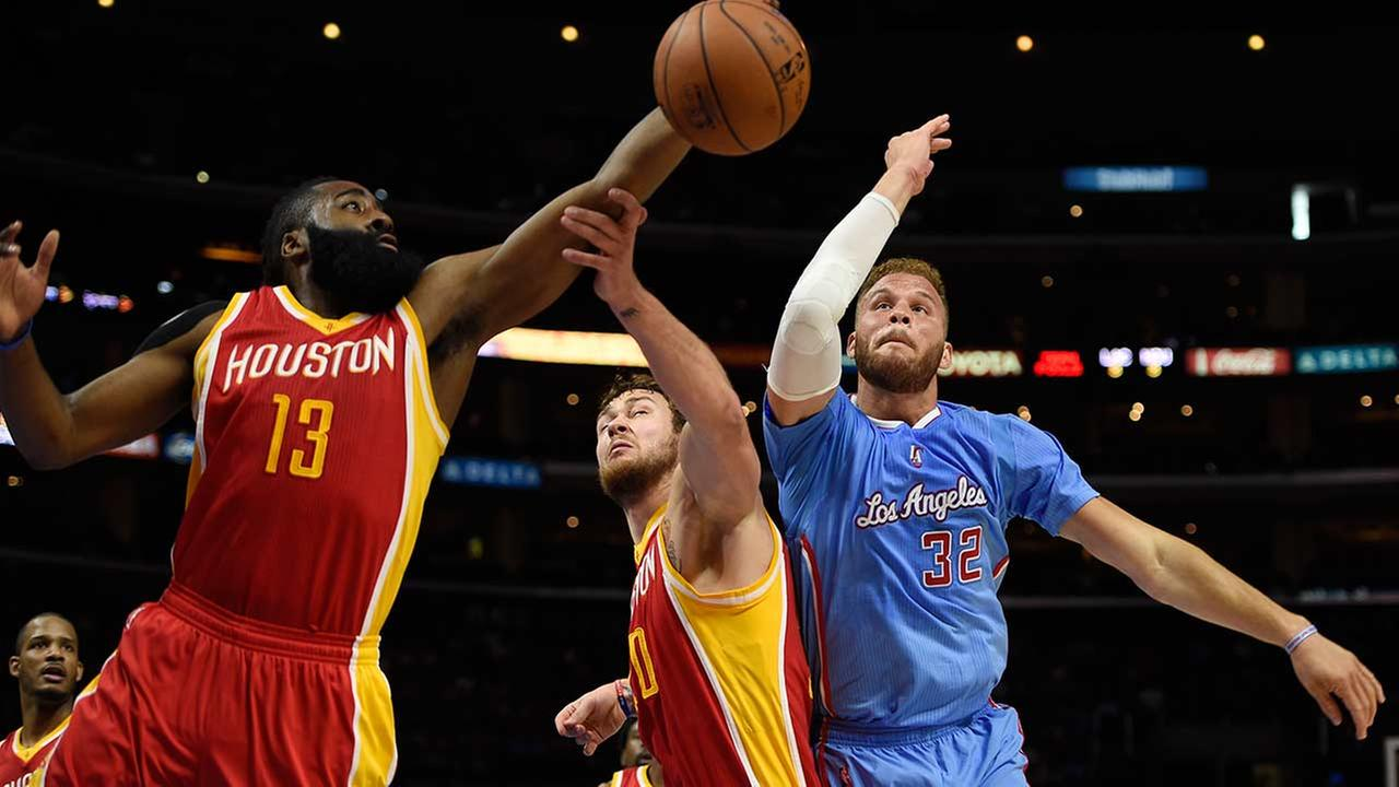 Houston Rockets guard James Harden, left, stretches to grab a rebound in front of forward Donatas Motiejunas, of Lithuania, center, and Los Angeles Clippers forward Blake Griffin.