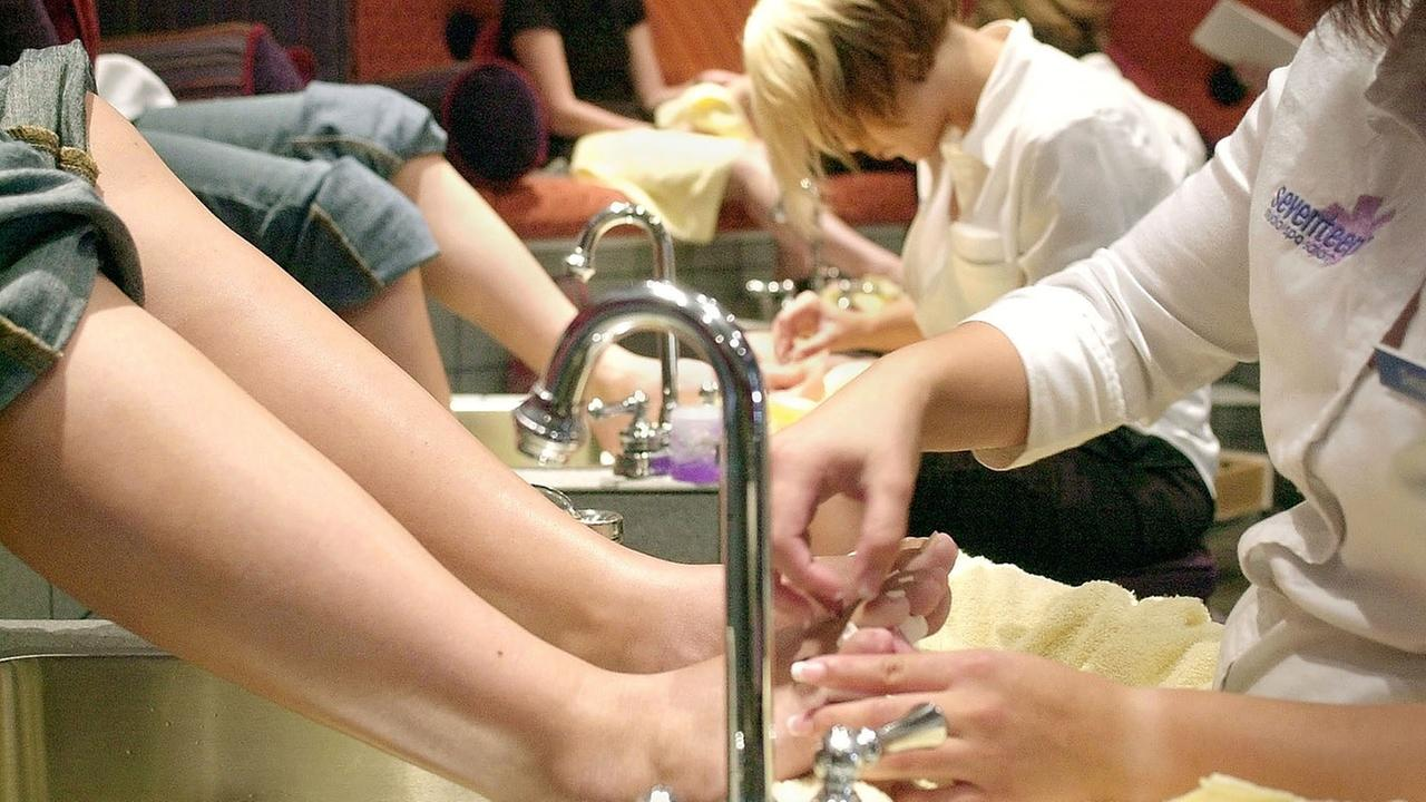 Young customers sit in a private room with plush red seats as they receive treatments from nail technicians