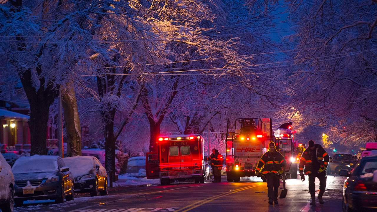 Firefighters walk near the scene of a fire, center left, in which seven children died in the Brooklyn borough of New York Saturday, March 21, 2015.