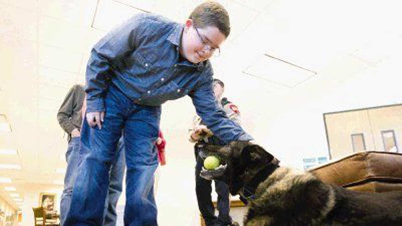 Bryce Everton pets Ranger, a german shepherd service dog with Montgomery County K9-Unit, as he chews on a tennis ball after being honored at the Montgomery County Commissioners Co.